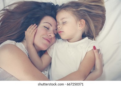 Young mother playing with her little daughter on bed. Enjoy together in free time.
