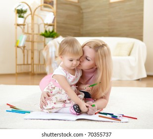 a young mother playing with her little baby at home