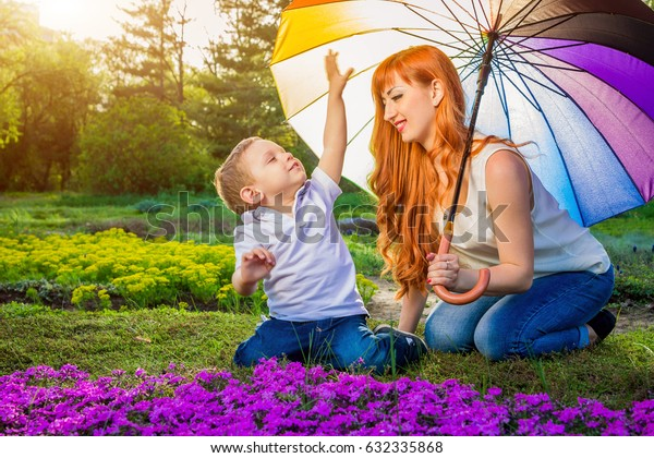 Young mother playing with her little son in spring garden. Mother's Day concept