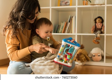 Young Mother playing with toddler at home