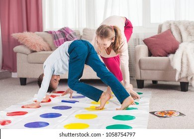 Young mother playing twister with her son. Cheerful family indoors. Happy family playing together