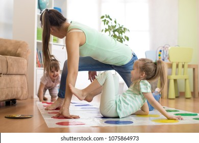 Young mother playing twister with her children daughters. Happy family have a fun time in holiday
