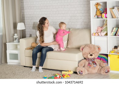 A young mother plays with a baby. A woman plays with a baby eight months of age