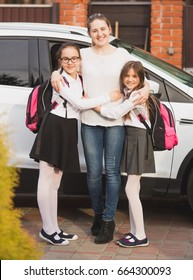 Young mother posing with daughters wearing backpacks next to the car