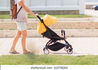 Young mother pushing stroller with sleeping baby by the street