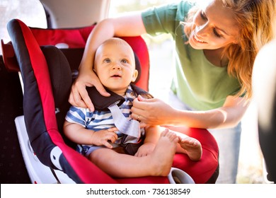 Young mother putting baby boy in the car seat.