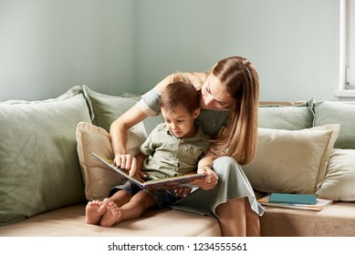 Young mother, read a book to her child, boy in the living room of their home, rays of sun going through the window