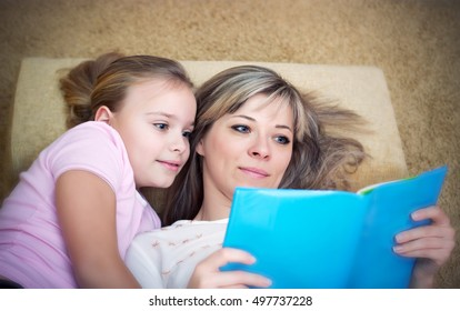 Young mother is reading a book to her cute daughter.