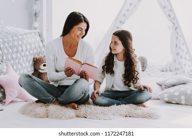 Young Mother Reading Book to Little Daughter. Beautiful Smiling Woman Sitting on Carpet Reading to Cute Adorable Daughter. Mom reads to Child at Home. Family and Motherhood Concept