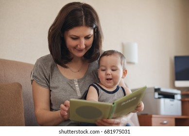 Young mother reading to her baby son who is reaching out to the book with obvious enjoyment indoors in the living room