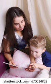 Young mother reads book for her little cute son among pillows, top view