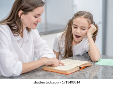 Young mother reads a book to yawning and lazy daughter at home