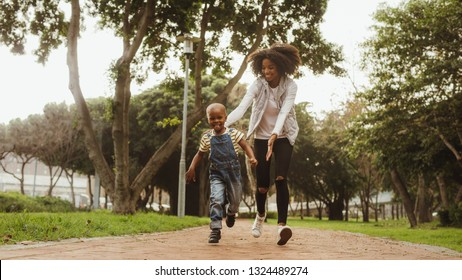 Young mother running with little boy in the park. Happy woman and cute kid having fun outdoors.