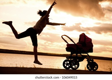 young mother is running to stroller with a baby at sunset