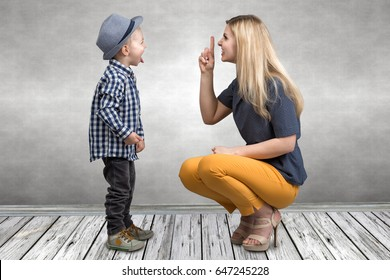 A young mother scolds her naughty little son.Boy showing tongue and teases mom.