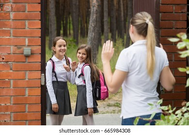 Young mother seeing her two daughters off to school at morning