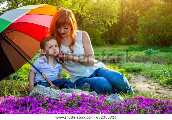 Young mother sitting with her little son in spring garden. Mother's Day concept
