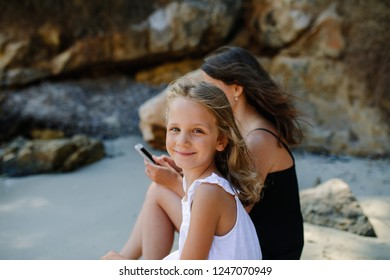 Young mother sitting on the beach and phubbing her daughter