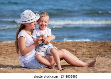 Young mother sitting on beach with son. Cute mom together child boy hugging, smiling, laugh, summer day. Happy childhood carefree playing on outdoor sand,sea, joy, fun. concept of holiday, vacation