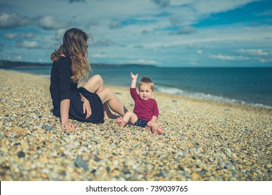 A young mother is sitting on a beach with her baby