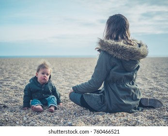 A young mother is sitting on the beach with her baby who is wearing a matching coat
