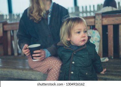 A young mother is sitting on a bench drinking coffee with her toddler