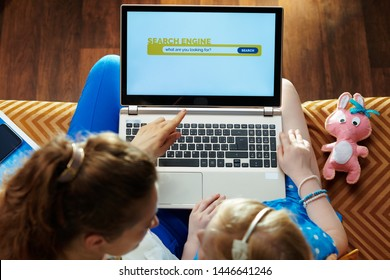 young mother sitting on sofa in the modern living room teaching daughter how to use search engine on a laptop.