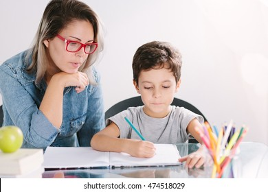 Young mother sitting at a table at home helping her small son with his homework from school as he writes notes in a notebook