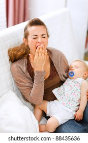 Young mother with sleeping baby on hands yawing at home
