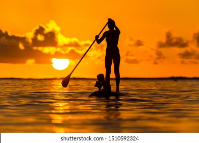Young mother with a small child ride a S.U.P. (paddle) board in the Indian Ocean on the background of an incredible sunset
