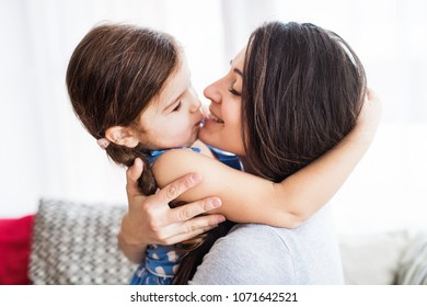 Young mother with a small girl at home.