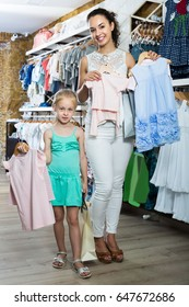 Young mother with small girl picking clothes in kids apparel store