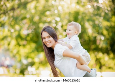 Young mother smiles holding baby on her back looking frame. Sunny day in park Happy family.