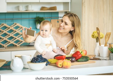 Young mother smiling, cooking and playing with her baby daughter in a modern kitchen. Healthy food concept. Working at home. Woman with a baby doing a selfie