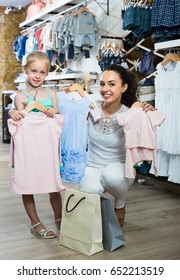 young mother with smiling daughter buying kids clothes in shop