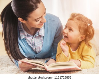 Young Mother and Smiling Daughter Lie on White Carpet and Reading Book at Home. Motherhood Concept. Leisure at home Concept. Family, love and happiness concepts. Childhood concept.