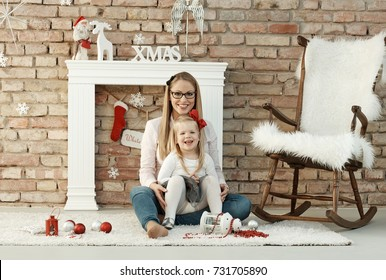 Young mother smiling happy with little daughter on her lap at christmas.