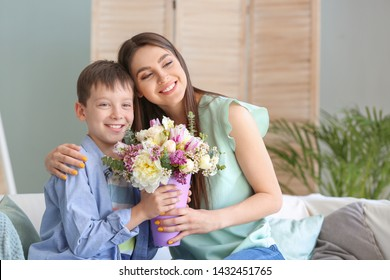 Young mother and son with bouquet of beautiful flowers at home
