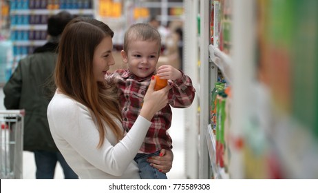 young mother and son buy water or juice in a store