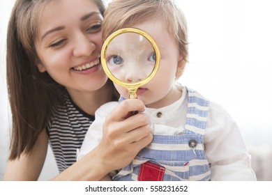 Young mother and son looking through a magnifying glass. Little boy with magnifying glass.