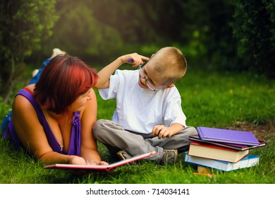 young mother and son lying on the meadow with book