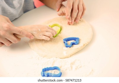 Young mother with son making biscuits on table