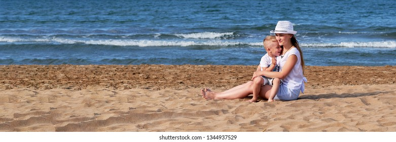 Young mother with son on sea beach. Child,girl siting coast. Mom together kid boy hugging,smiling,summer day, lifestyle. Sand,ocean background. Panoramic,banner, copy space. concept holiday,vacation.