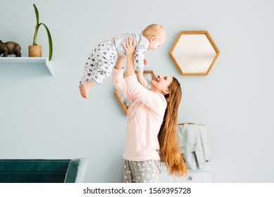 Young mother and son are playing in the bright room of his house. Cute baby boy with his mom. Happy and cute family chatting with baby
