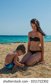 young mother and son playing on the beach. family on vocation. Mother plays with her baby on the beach. A woman with her son on the seashore.
