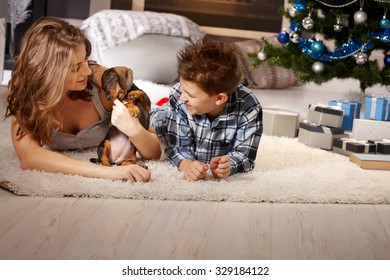 Young mother and son playing with puppy at christmas time, lying on floor.