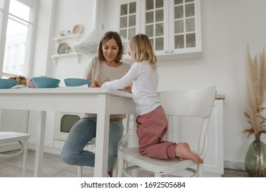 A young mother spends time with her little daughter at home. Breakfast, motherhood, family concept.
