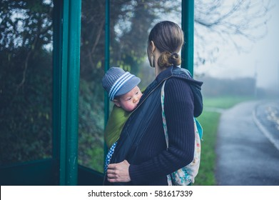 A young mother is standing at a bus shelter with her baby in a carrier sling