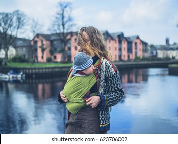 A young mother is standing by a river with her baby in a carrier sling