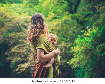 A young mother is standing in nature with her baby in a sling
